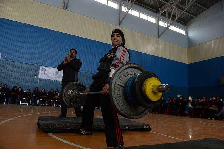 Een Afghaanse vrouw neemt deel aan een competitie gewichtheffen ter gelegenheid van Internationale Vrouwendag. Beeld null