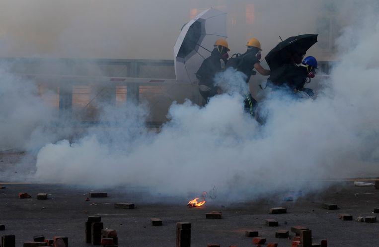 Demonstranten rennen weg van het traangas dat de politie afvuurt aan de universiteitscampus. Beeld REUTERS