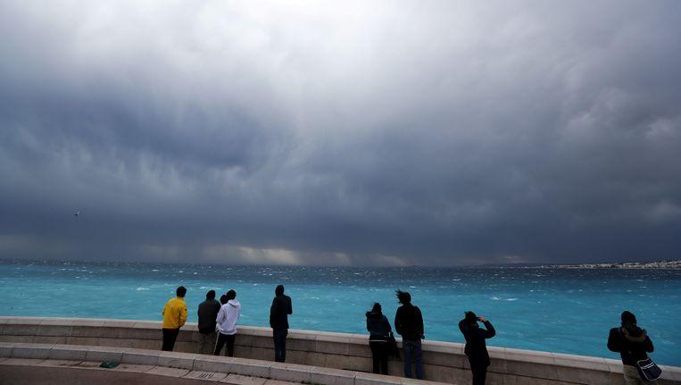 Toeschouwers kijken terwijl terwijl een storm nadert in Nice. Beeld AFP