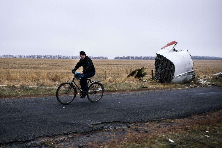 Een inwoner van Hrabove fietst op 7 november langs brokstukken van vlucht MH17. Beeld AFP