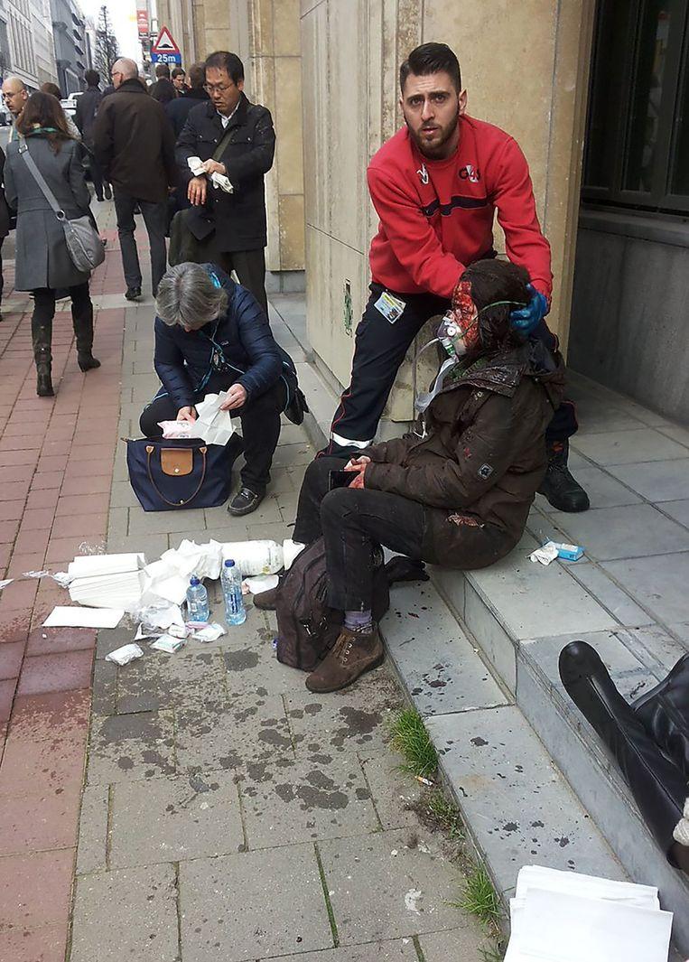 Een beveiliger helpt een gewonde vrouw buiten metrostation Maalbeek. Beeld afp