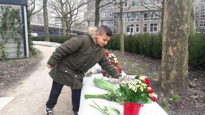 De 9-jarige Noah van Bommel legt bloemen bij het 24 Oktoberplein in Utrecht, een jaar na de tramaanslag.