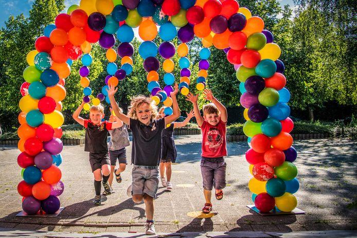 Kleuters worden met ballonnen ontvangen op een school. Archiefbeeld.
