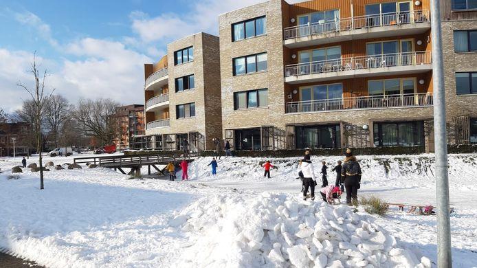 Kinderen spelen op het ijs en in de sneeuw, onbewust van het drama dat zich eerder op de dag in het appartementengebouw heeft voltrokken in Bennekom.