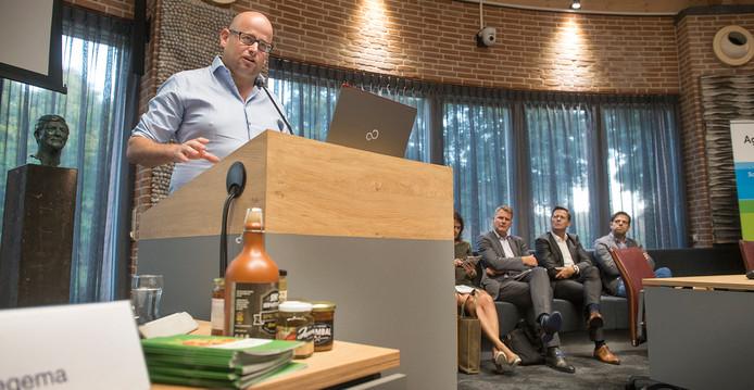 Bram Voets van Voets Specialiteiten geeft een presentatie. Op de achtergrond René Peerenboom, de nieuwe regiomanager van AgriFood Capital (tweede van rechts).