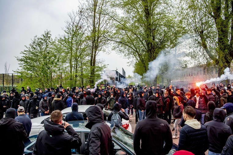 Feyenoord-fans bekogelen de politie met vuurwerk en stenen tijdens een training van de club. Beeld ANP
