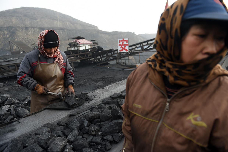 Chinese mijnwerkers sorteren brokken steenkool in een mijn in het noorden van China. De afgelopen vier jaar daalde het aandeel steenkool in de elektriciteitsopwekking van 69 naar 57,5 procent. China meldde onlangs ernaar te streven om in 2060 klimaatneutraal te zijn.