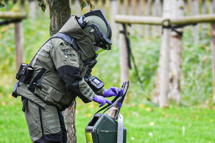 Een medewerker van de EOD checkt of het verdachte pakketje in de afvalbak op Urk explosieven bevat.