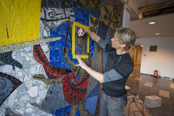 Specialist Arno van Sabben haalt het mozaïek stukje bij beetje van de muur.