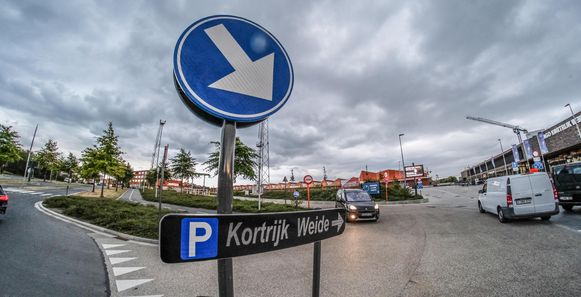 Het bord 'P Kortrijk Weide' lijkt rechtstreeks naar de brede laan aan het zwembad Weide zelf te wijzen. Terwijl je om correct te zijn links moet meedraaien om de parking op het Mandelaplein op en af te rijden.