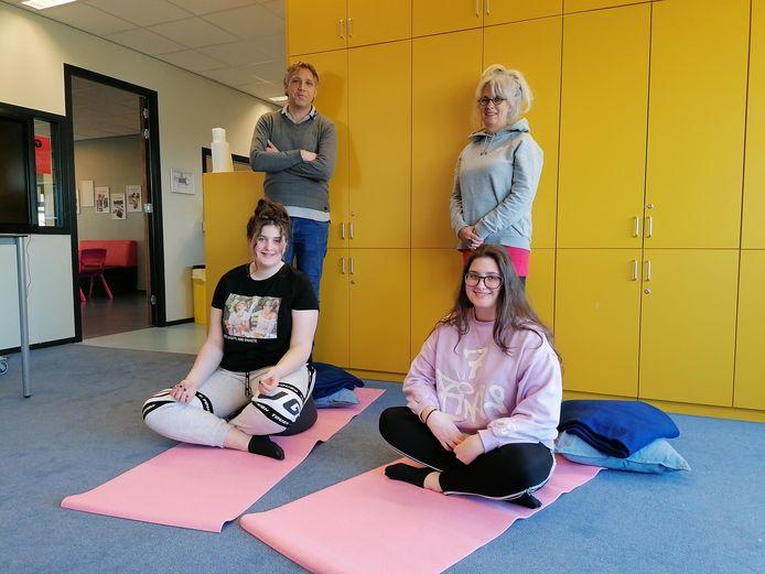 Teamleider Rene Kilian en yogadocente Brenda Schot met op de yogamatjes leerlingen Anna en Maria. ,,We leren door yoga stevig in onze schoenen te staan en rustig te blijven.''