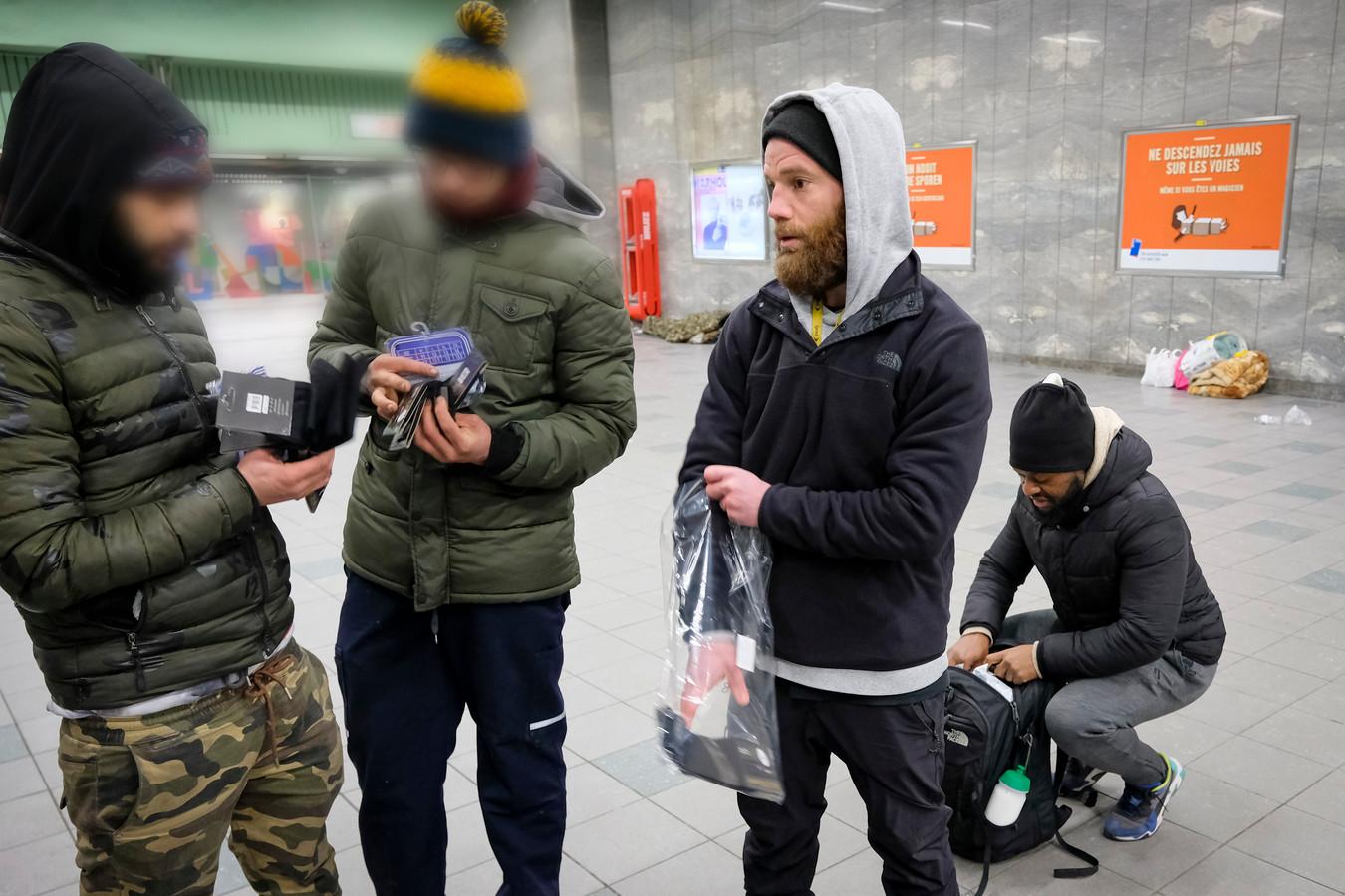Romain en Arnol geven sokken aan daklozen in het metrostation.