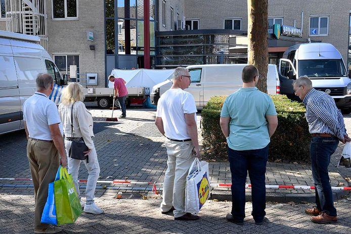 Mensen die nietsvermoedend boodschappen doen in het winkelcentrum, bekijken achter rood-witte linten de ravage. Er is vooral ongeloof.