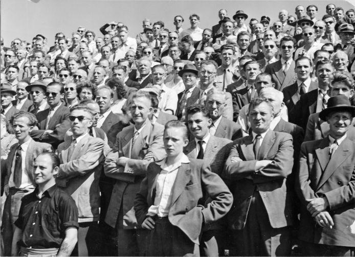 Mannen en jongens in pak, stropdas om, peuk in de mondhoek. Supporters in het Arnhemse stadion Nieuw-Monnikenhuize aan de Rosendaalseweg omstreeks 1960.