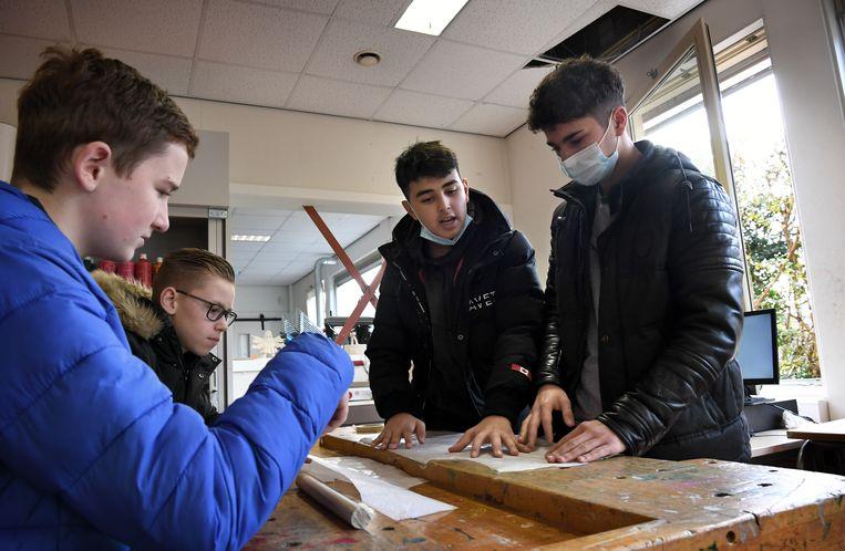 Leerlingen van een school in Tiel werken met jas aan in de klas, omdat de ramen open staan voor de ventilatie.  Beeld Marcel van den Bergh/de Volkskrant