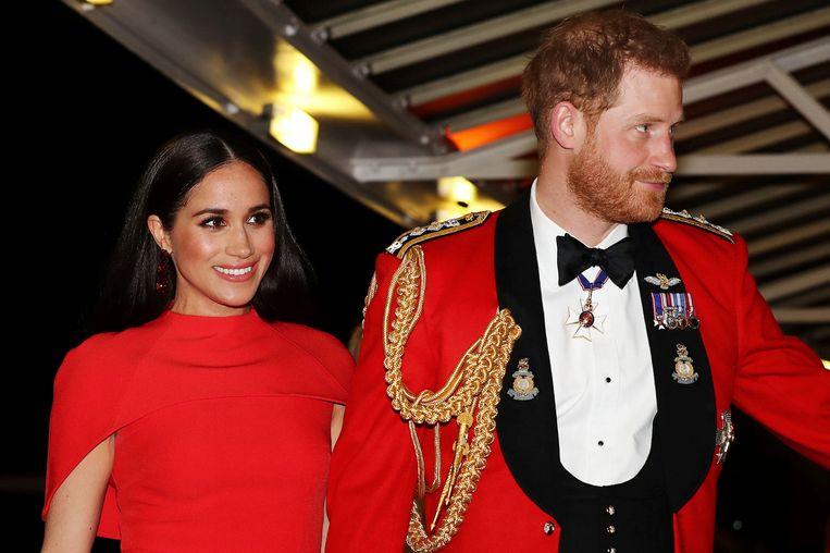 Meghan en Harry komen aan in de Royal Albert Hall in Londen voor het Mountbatten Festival of Music, in 2020. Beeld AP