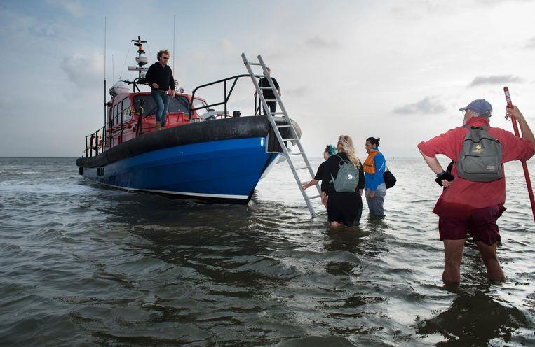 Jelle Bos pikt de doorweekte groep met zijn boot op. Beeld Els Zweerink
