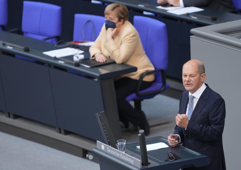 Minister van Financiën Olaf Scholz aan het woord in de Bondsdag. Kanselier Angela Merkel luistert. Beeld Kay Nietfeld/dpa