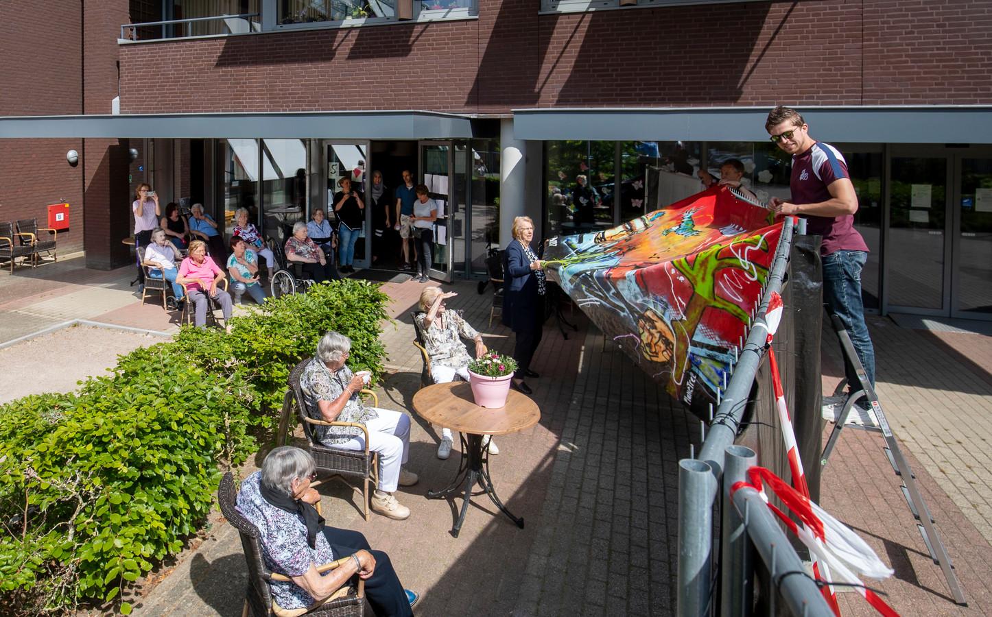 Kunstenaar MilantheArtist biedt de bewoners zorgencentrum St Barbara een kunstwerk aan.