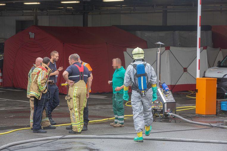 Brandweermannen in beschermingspakken hielpen de mensen bij het nemen van de douche.