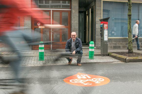 Schepen Carl Hanssens bij de ingang van een fietsparking van een school in de Ankerstraat, waar zo'n nieuwe sticker is aangebracht.