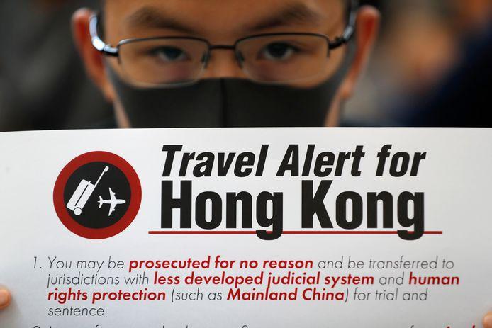 Een demonstrant toont een van de vele slogans tegen de groeiende invloed van China in de voormalige Britse kroonkolonie.