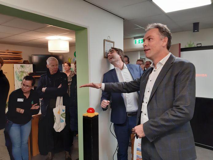 Wethouder Geert Gerrits (rechts) en Talis-bestuurder Ronald Leushuis (tweede van rechts) kijken naar het resultaat van hun openingshandeling, een klap op de rode knop...
