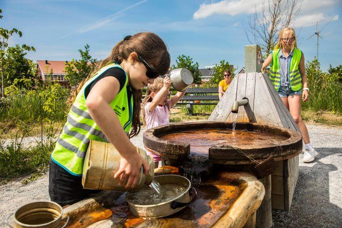 Joya, Lola en Janne spelen met water dat ze zelf oppompen in de natuurspeeltuin van De Weidemolen.