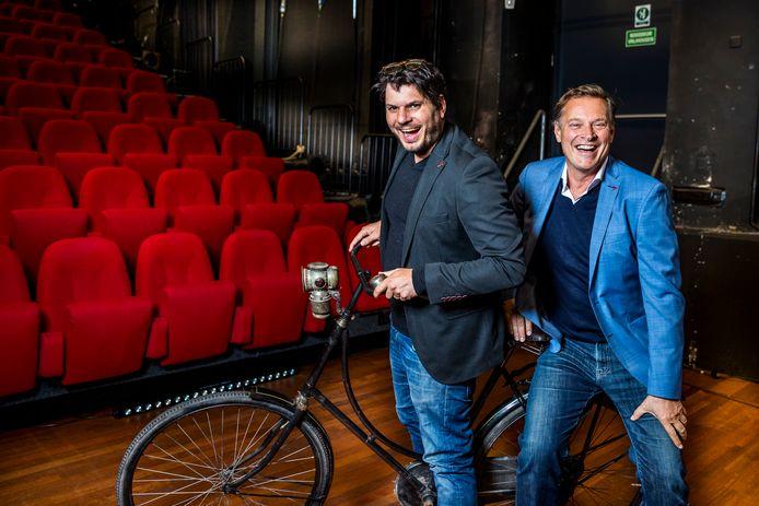 Serve Hermans (L) en Albert Verlinde (R) samen op de welbekende fiets van kapelaan Odekerken. Samen gaan ze de grootschalige musical Dagboek van een Herdershond op de planken brengen.