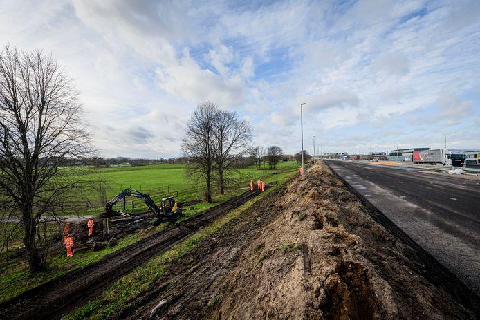 Medewerkers van aannemer Heijmans planten boompjes in langs de A1, ter hoogte van Enter.