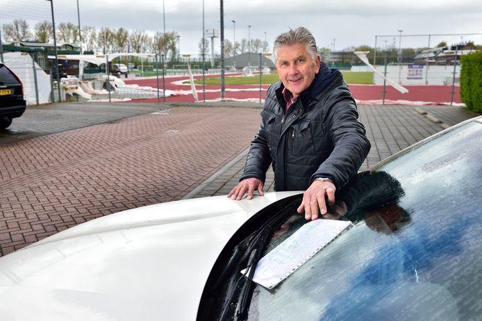 Wim Plokkaar bij zijn beschadigde auto.