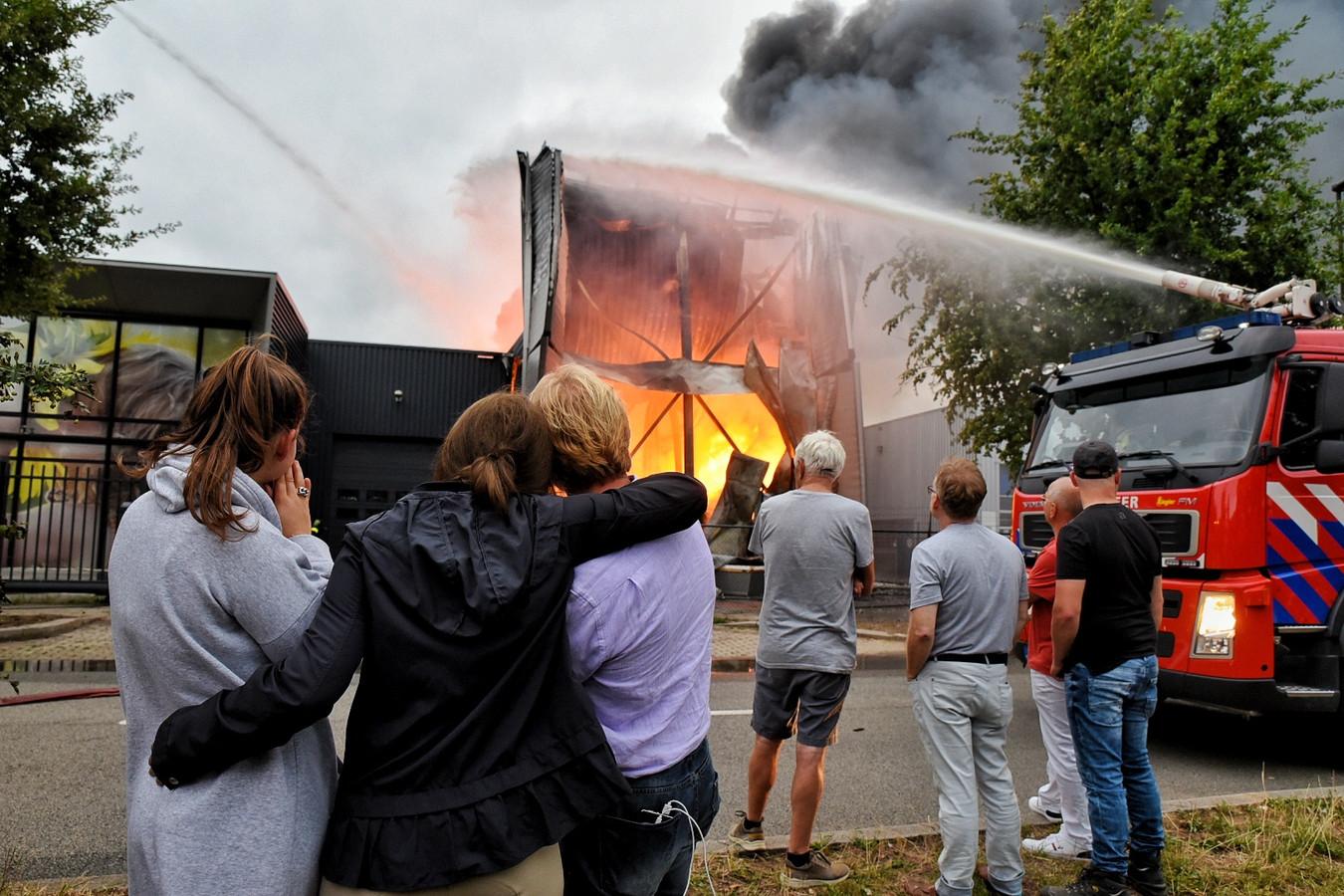Directeur Kees van Opstal (derde van links) kijkt in 2019 toe het vuur de hal bij zijn bedrijf Fire-Up, op bedrijventerrein Laarakkers in Oisterwijk, verwoest.