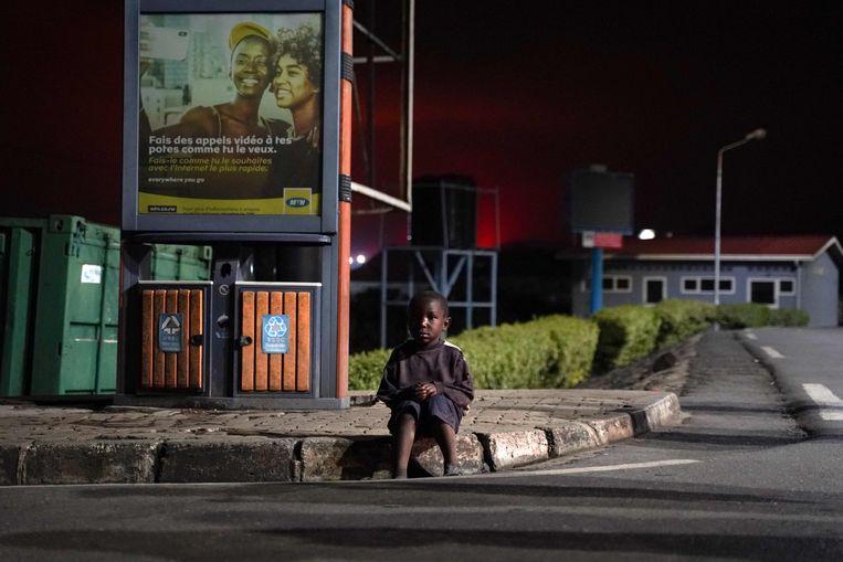 Een verloren kind zit op een straathoek in het Rwandese Gisenyi, net over de grens met Congo. Na de eruptie van de Nyiragongo-vulkaan zijn veel Congolezen uit de nabijgelegen grensstad Goma op de vlucht geslagen.  Beeld AFP