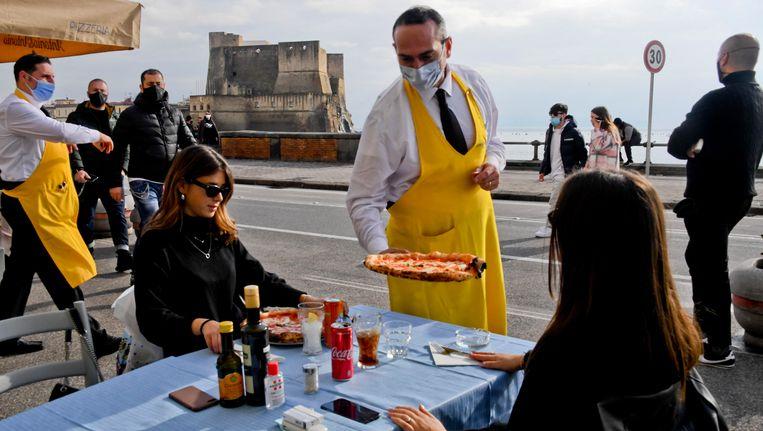 Pizza begin januari in Napoli. Italië zit in een regeringscrisis, maar de Italianen vieren de terug in de gele zone van de coronacrisis. Beeld EPA