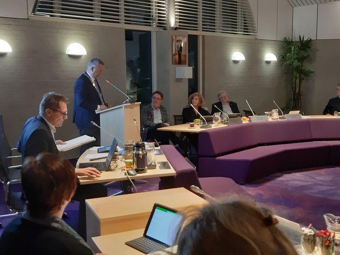 Burgemeester Mark van Stappershoef sprak Bert Schellekens (rechts langs spreekgestoelte) toe tijdens zijn afscheid van de gemeenteraad.
