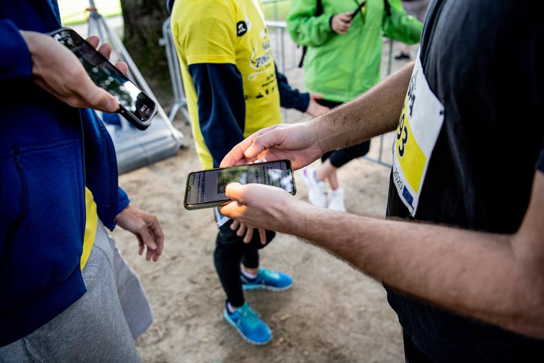 Net zoals op de meeste (grote) evenementen moesten de deelnemers aan de 20 kilometer van Brussel hun 'coronapas' laten zien.  Beeld Photo News