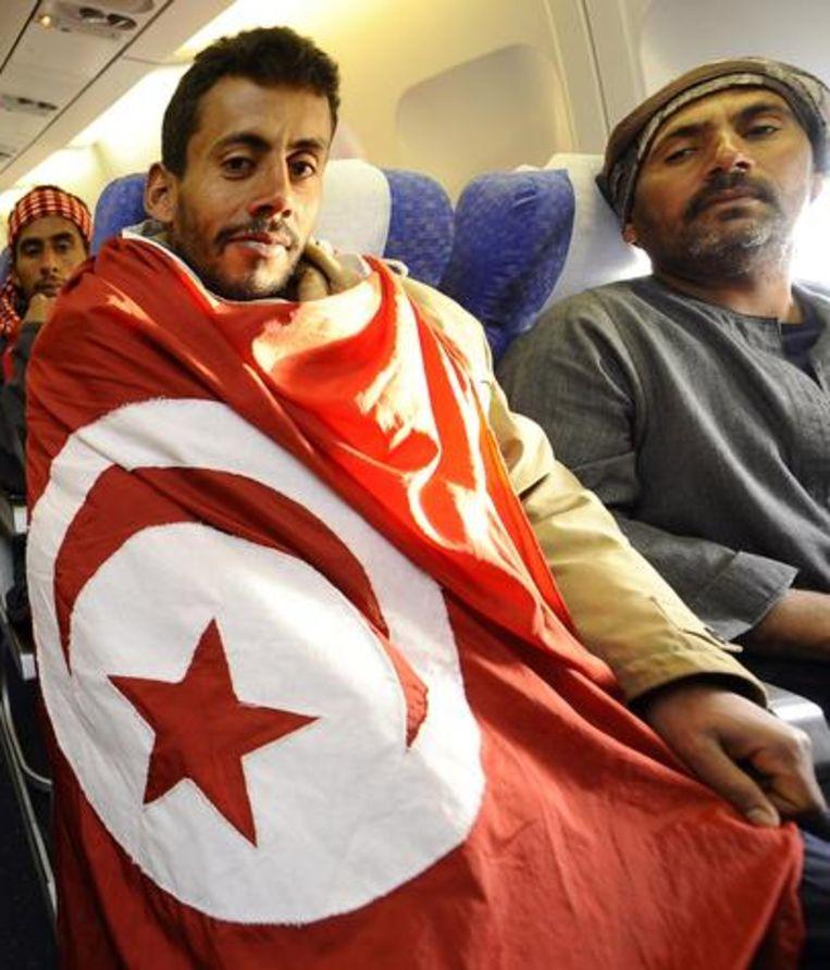 Deze Egyptische vluchteling bracht een Tunesische vlag mee als souvenir. Beeld BELGA