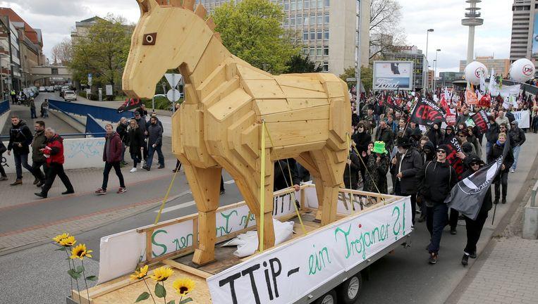 Duitsers slepen een houten paard mee, symbool van wat de demonstranten als het Paard van Troje zien: het TTIP-handeslverdrag. Beeld epa
