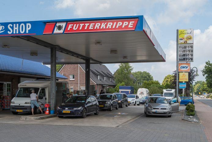 Een rij gele nummerborden staat tot op het fietspad klaar om voor 1,52 per liter benzine te tanken in het Duitse Itterbeck.