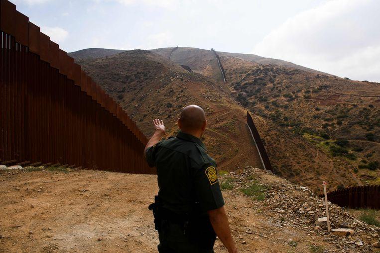 Een Amerikaanse grenswacht wijst de muur tussen Amerika en Mexico aan.   Beeld AFP