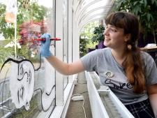 Lotte schildert kunstwerk op Nijkerkse bibliotheek: 'Ik probeer corona in het straatbeeld te brengen'