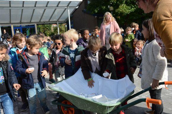 De leerlingen mochten elk een steentje met daarop hun naam in een kruiwagen leggen.