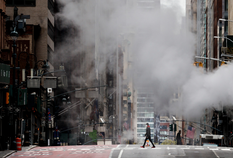 Een voetganger steekt de verlaten Madison Avenue over in New York. De stad is het epicentrum van de corona-uitbraak in de VS.