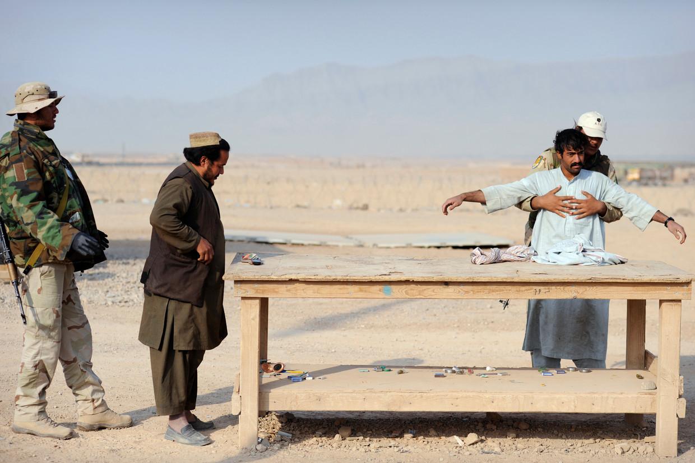 Bezoekers van Kamp Holland in Tarin Kowt, Uruzgan, Afghanistan worden gefouilleerd voor ze het kunnen betreden; 2009.