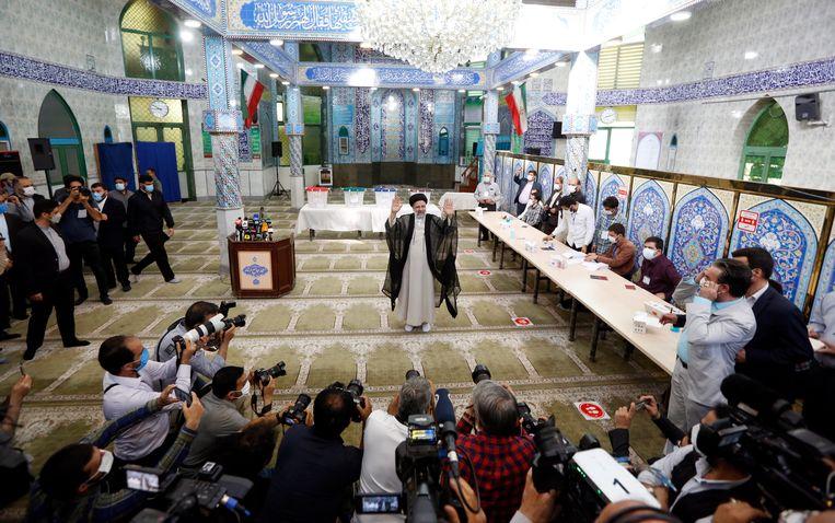 Ebrahim Raisi zwaait naar de camera's van de aanwezige mediavertegenwoordigers, kort nadat hij vrijdag in Teheran zelf zijn stem heeft uitgebracht bij de verkiezingen. Beeld EPA