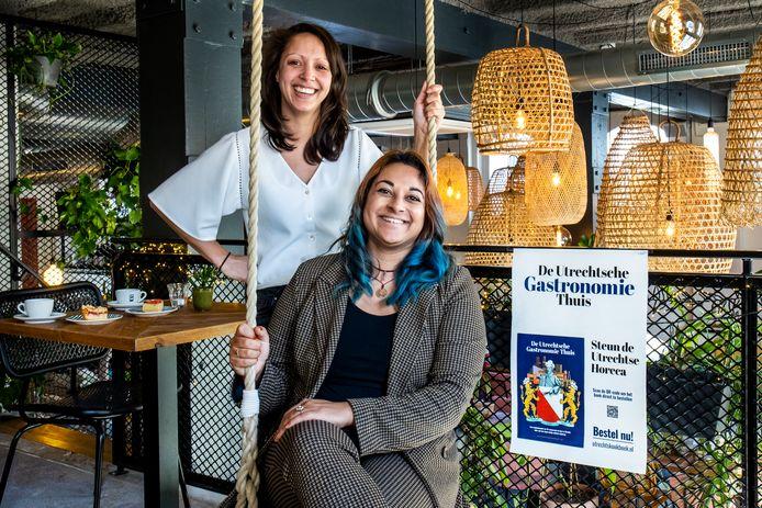 Kiki Mossink (28) (links) en Nadia Khaleghi (31) maakten samen het kookboek De Utrechtse Gastronomie Thuis om de Utrechtse horeca te steunen. De foto is gemaakt in Karibu.