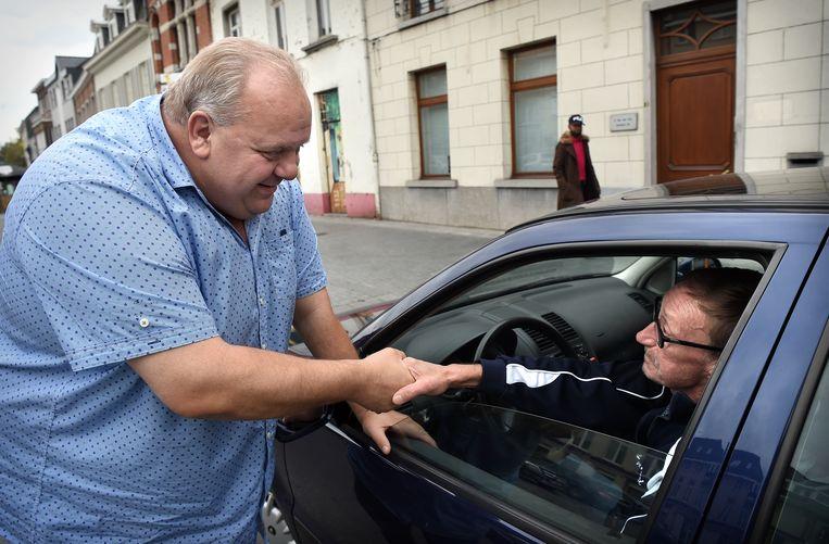 Guy d'Haeseleer van Vlaams Belang en partij Forza Ninove wordt door een voorbijganger gefeliciteerd met zijn behaalde verkiezingsresultaat. Beeld Marcel van den Bergh
