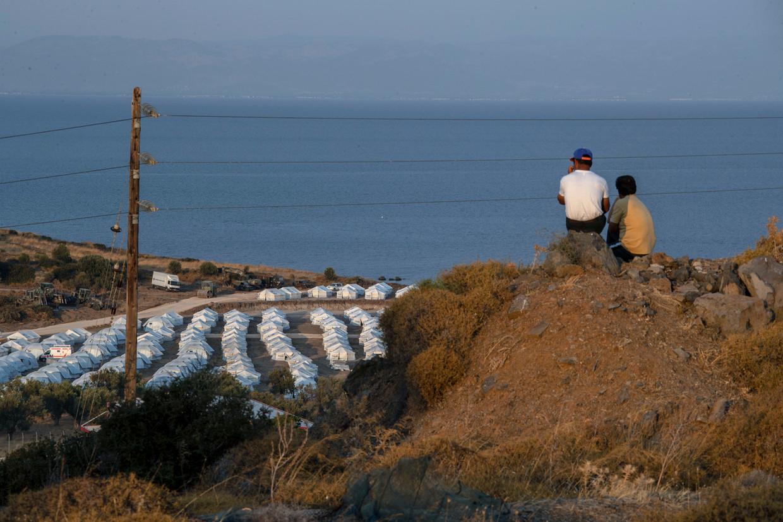 Vluchtelingen en migranten kijken uit over het nieuwe tijdelijke (?) kamp dat na de brand van Moria is opgericht.