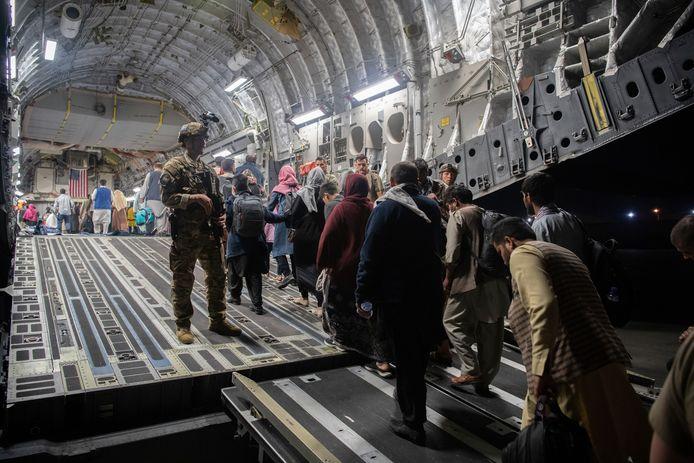 Afghaanse evacués gaan op het vliegveld van Kaboel aan boord van een Amerikaans vliegtuig.