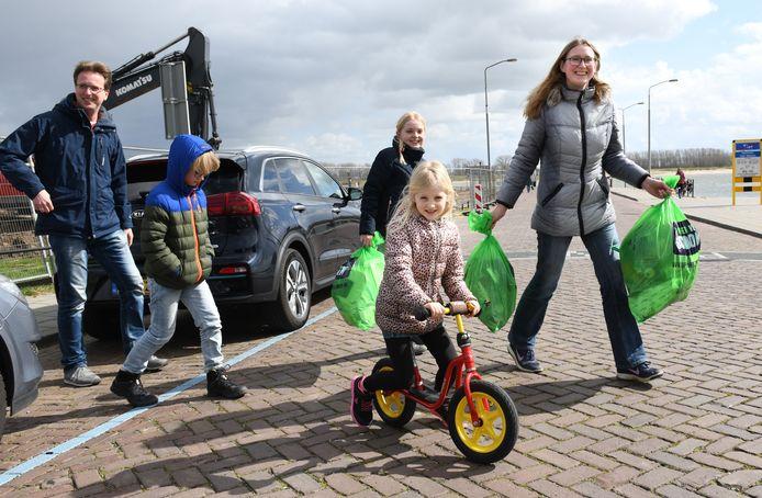 Een gezin brengt zwerfvuil naar het inzamelpunt aan de Waalkade in Tiel.